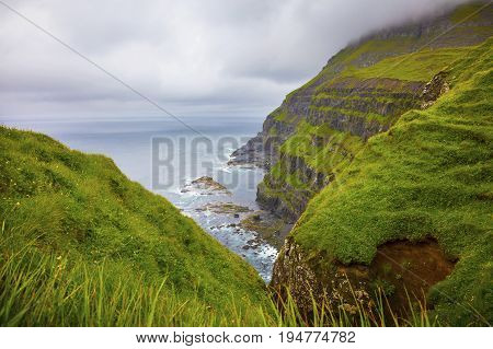 Dramatic landscape on a cloudy day at Faroe Islands, Danmark. Rainy day in july.