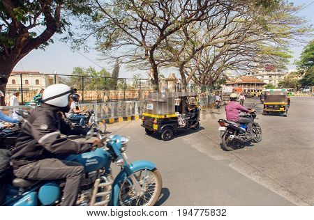 MYSORE, INDIA - FEB 17, 2017: Taxi rickshaw and motorcycles under trees of the old streets of indian city on February 17, 2017. Mysore of Karnataka has a population of 900000