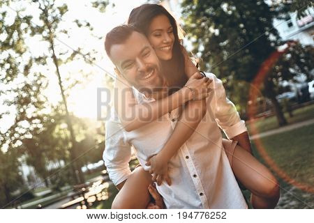 Falling in love. Handsome young man carrying young attractive woman on shoulders while spending time together outdoors