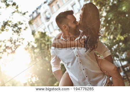 Expressing true love. Handsome young man carrying young attractive woman on shoulders while spending time together outdoors