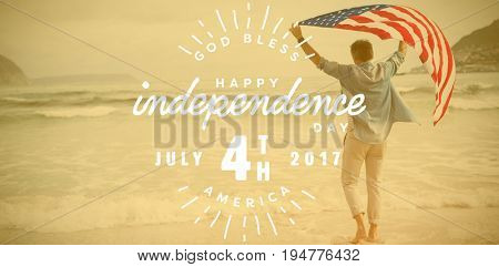 Digitally generated image of happy 4th of july text against man carrying american flag on shore