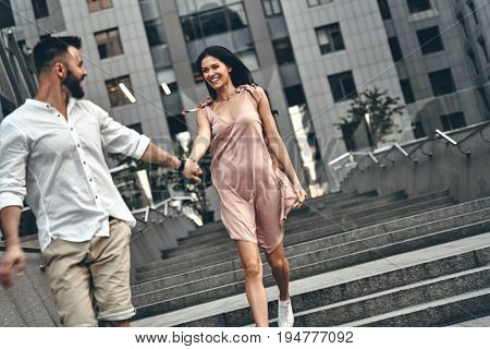 Two hearts full of love. Beautiful young couple holding hands and smiling while walking down the stairs outdoors
