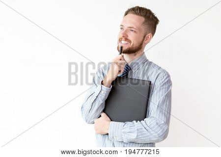 Portrait of young Caucasian businessman wearing shirt and necktie standing with pensive expression holding leather folder and pen and smiling
