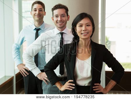 Closeup portrait of three smiling young business people looking at camera and standing with hands on hips one after another near office window. Woman is in front of two men. Front view.