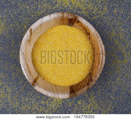 Corn meal of dry polenta on dark background. Flat lay style.