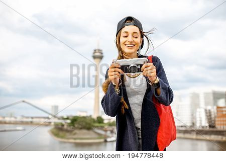 Young woman tourist standing with photo camera with famous television tower and modern buildings in Dusseldorf city, Germany