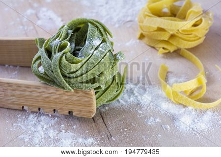 Green and yellow pasta on wooden table with flour