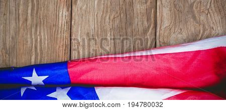 Creased US flag against close-up of wooden texture