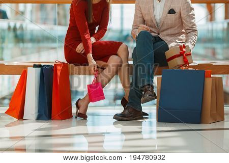 Young couple with shopping bags resting in mall