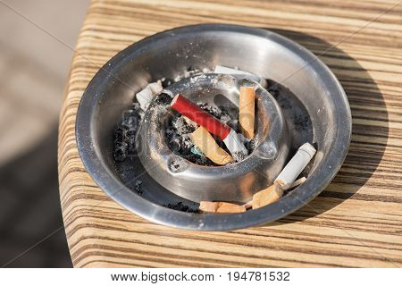 Silver ashtray with cigarette butts on a horeca table outside on a sunny day