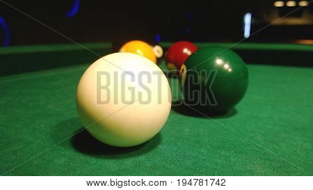 Billiard balls for pool are on the table near the pockets