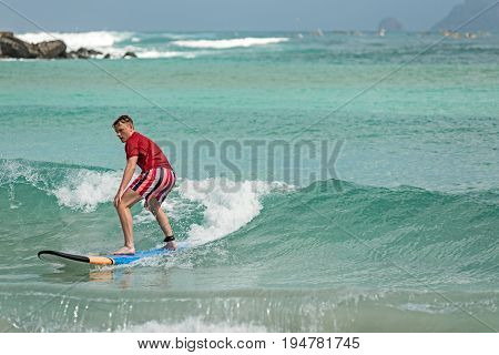 10/06/2017 Pantau Mawun Lombok Indonesia. Young man learns to surf on a long board on learner waves in a paradise location.