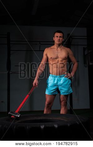 Portrait of handsome muscular young man working out with huge tire and hummer. Weightlifting or functional training. Sports and fitness concept.