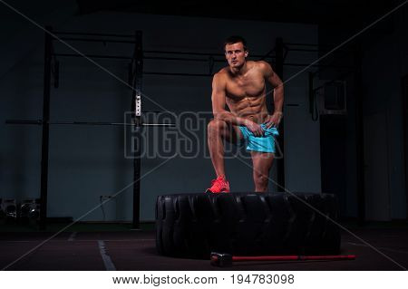 Portrait of confident young man with naked torso exersicing with hummer and tire. Weightlifting or functional training. Sports and fitness concept.