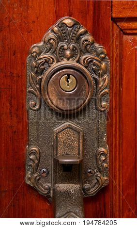 Key hole on brass handle on wooden door.