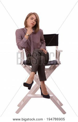 Sirious young blonde woman sitting on a chair holding her hand under her chin isolated on white background