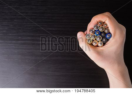 Colored batteries in hand close-up. To save energy. AA alkaline batteries. Colored batteries. Ecological batteries. Litter the nature of batteries