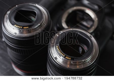 Two lenses and a camera mount. Contacts of the microprocessor on the lens for connection to the camera. Photo lens. Black autofocus lens. The lens is on the table. Conceptual photography with a lens