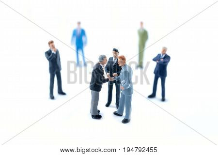 Miniature people shaking hands Business concept .