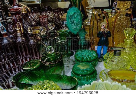 Moscow, Russia - March 19, 2017: Figurine of the caster of snakes playing on a pipe made of colored glass surrounded by colorful vintage glassware. Old objects from glass is popular with collectors.