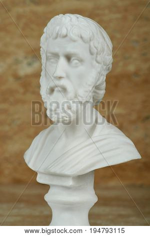 Statue of Sophocles, ancient Greek poet on brown background.