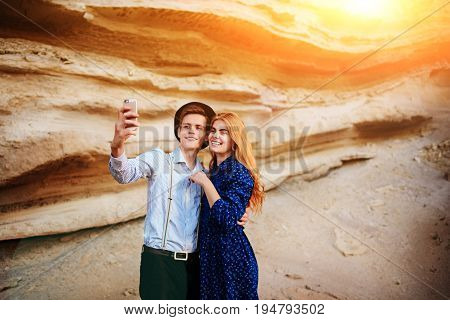 Attractive Man With A Beautiful Woman Are Hugging And Smiling. They Are Making Selfie On The Backgro