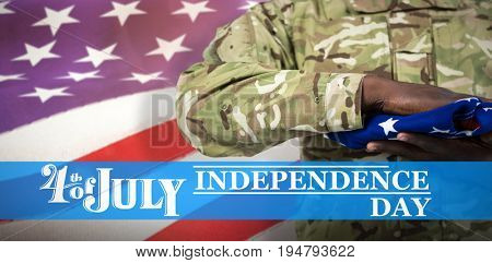 Mid section of soldier holding american flag against waving flag of america