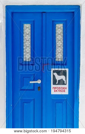 A traditional blue door on the cyclades islands with beware of the dog