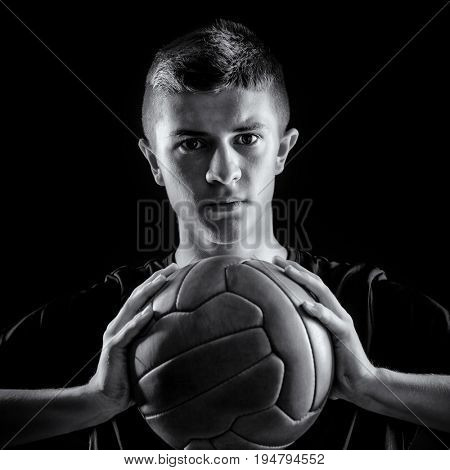 portrait of soccer player holding vintage leather ball