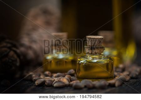 Oil of cedar nuts on a dark wooden background