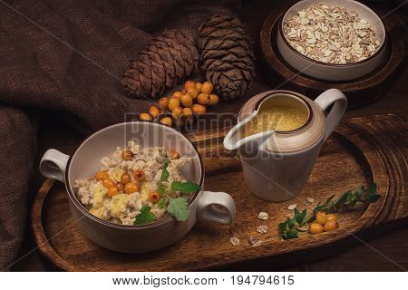 oatmeal with sea buckthorn butter and greens with pine nuts and sauce