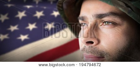Close up of thoughtful soldier against cropped american flag