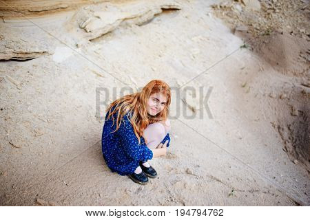 Woman With Long Carrot Hair Is Crouching And Hugging Herself In The Middle Of A Sandy Canyon