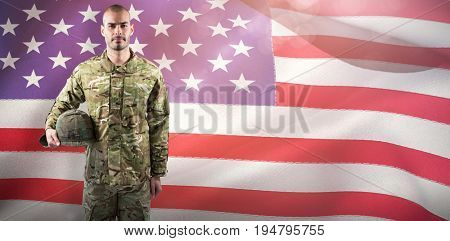 Portrait of confident soldier with helmet  against close-up of american flag