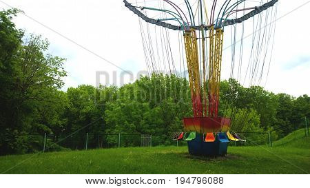 Detached entertainment amusement Park ride. Seats on long chains. Nobody rides. Around the silence and the forest.