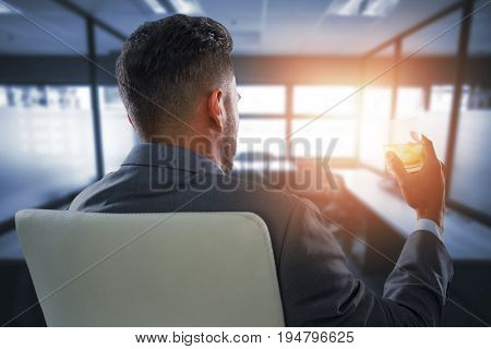 Rear view of businessman holding whisky glass against table and empty chairs in office