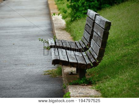 Wooden benches by the walkway Two wooden benches side by side by a concrete walkway in a park