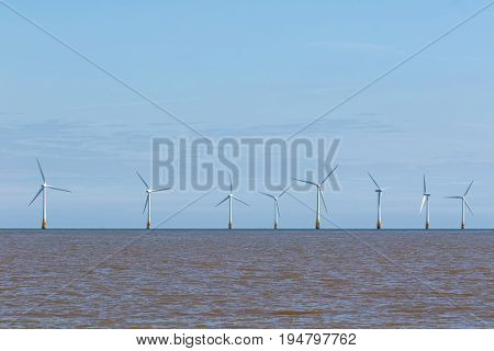 Offshore wind farm turbines on the sea horizon. Clean energy poster or banner image against blue sky with copy space.