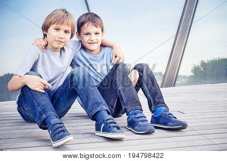 Two happy funny kids sitting together and embracing