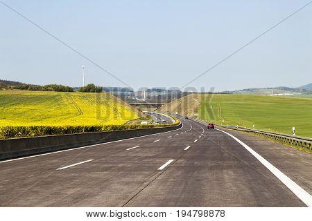 Brand new freeway road in Germany. Motorway between green fields in summer day