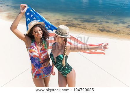 Two happy young women in beach wear and straw hats are standing close to each other on seashore and holding national american flag. They are smiling and european girl is looking at mulatto