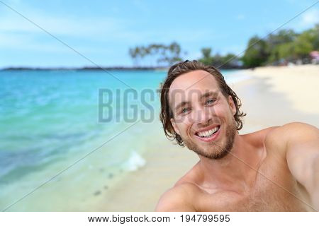 Beach selfie man on summer travel Hawaii vacation vlogging taking self-portrait video or picture as social media vlogger online.