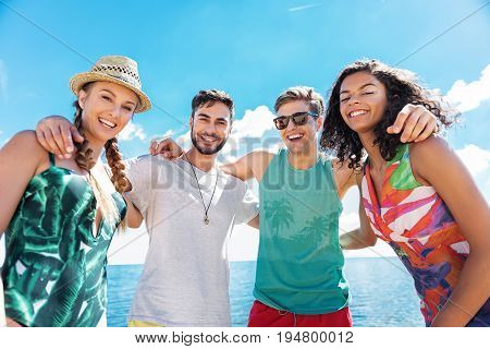 Waist up portrait of four young jolly men and women standing on river shore and hugging each other. They are laughing and smiling broadly