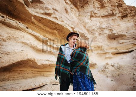 An Attractive Man Hugs A Beautiful Woman. The Pair Wrapped In Plaid In The Middle Of A Sandy Canyon