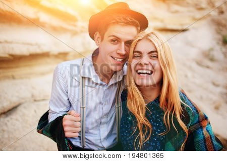 Handsome Man And Beautiful Woman Smiling Into The Camera In The Middle Of A Sandy Canyon