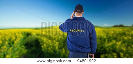 Rear view of security officer listening to earpiece against yellow mustard field