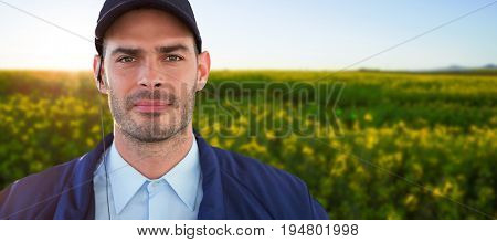 Portrait of handsome security officer against scenic view of beautiful mustard field