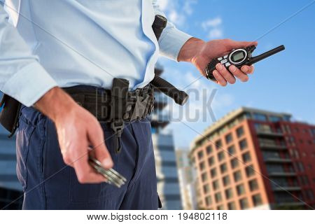 Mid section of security officer holding hand cuff and walkie talkie against modern buildings against sky