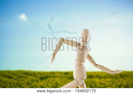 3d image of wooden figurine running against flock of bird flying over field