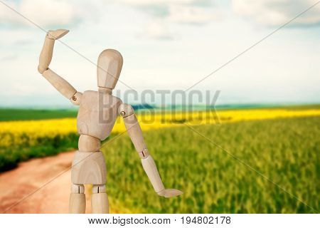 Wooden 3d figurine standing with hand raised against scenic view of empty path passing through fields
